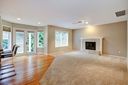 empty space: Large bright empty new living room with fireplace and beige carpet.