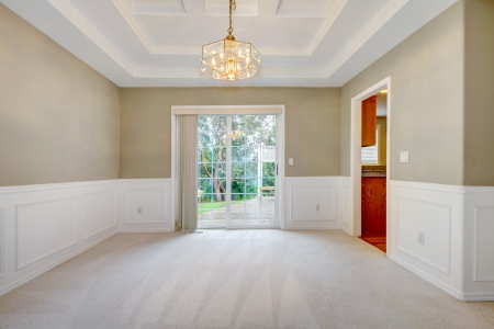 Empty luxury home interior with beige carpet of dining and living room.
