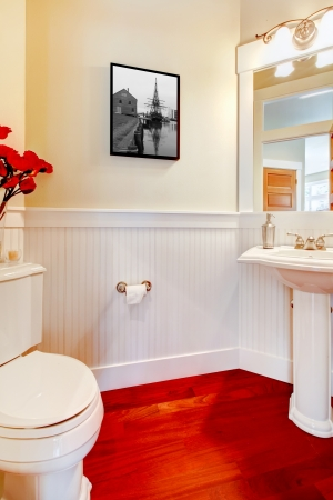 White small elegant bathroom with red wood floor and mirror. photo