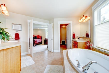 Large bathroom with white tub and open door to bedroom and closet. photo