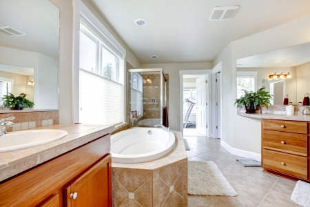 white wood floor: Large bathroom with tub and wood cabients and gym view. Stock Photo