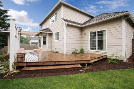 wooden deck: Large beige house with porch from the backyard with grass and mulch.