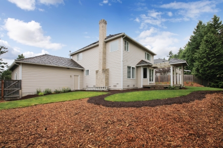 bark mulch: Large beige house with empty backyard during spring with mulch and grass. Stock Photo