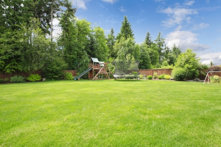 Summer fenced backyard with play ground area and trees and large lawn. Stock Photo - 15961217