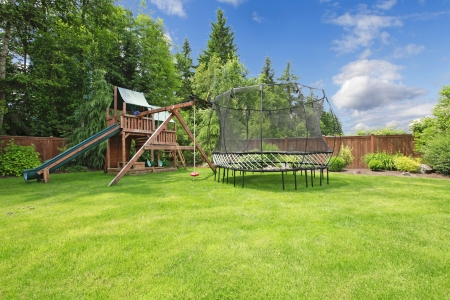 fenced: Play kinds ground area with tremplin in fenced backyard during summer.