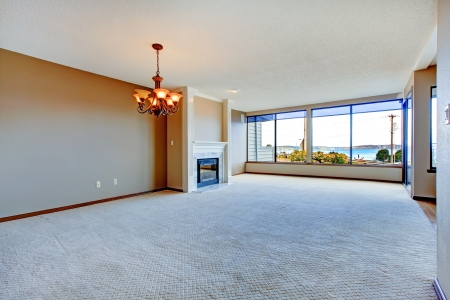 furnished: Apartment living room with large windows, carpet and hardwood floor  Stock Photo