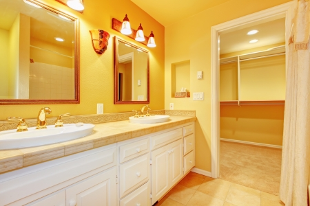 Bathroom with white cabinets and gold yellow walls with two mirrors  Stock Photo - 16306546