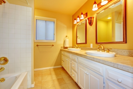 Bathroom with white cabinets and gold yellow walls with two mirrors  Stock Photo - 16306548
