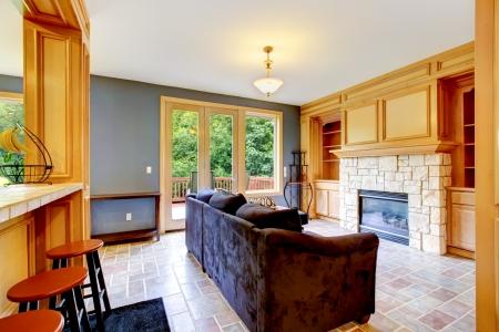 balcony door: Sal�n con paredes azules, chimenea y sof� marr�n con puerta balc�n grande