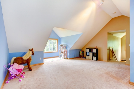 room: Blue attic living room with toys and play area with vaul ceiling