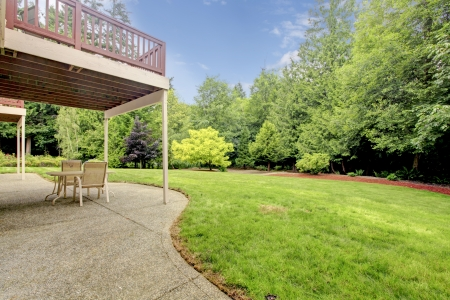 lawn chair: Backyard of the houes with porch and green forest with large lawn area