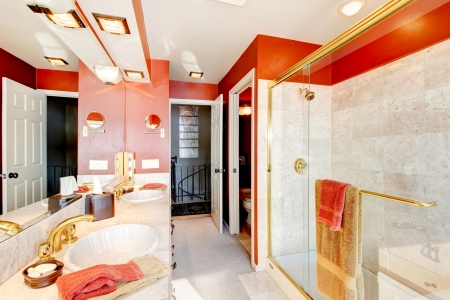 Bathroom with red walls and walk-in shower with beige tiles