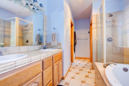 Blue large bathroom with tub and shower and wood cabinets  photo