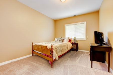 Large bedroom with yellow walls and beige carpet with TV  Banco de Imagens