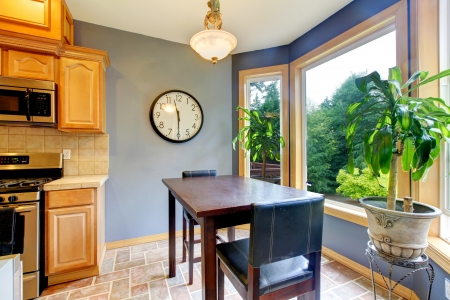 Dining breakfast table near the kitchen with blue walls and green backyard view Stock Photo - 16335355