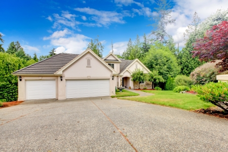 Large beautiful beige and grey house exterior during summer with large driveway