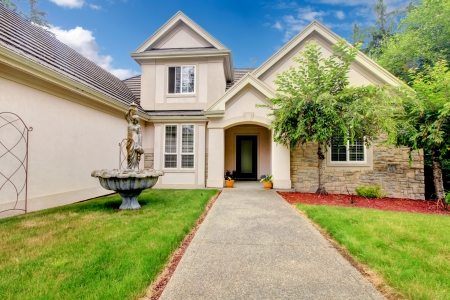 front house: Large beautiful beige and grey house exterior during summer