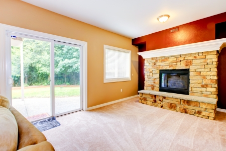 Empty yellow and red Living room with large fireplace and door to backyard  photo
