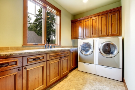 laundry room: Luxury laundry room with wood cabinets and tile floor.