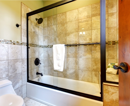 Top quality shower bath tub with stone tiles and toilet with wood door.