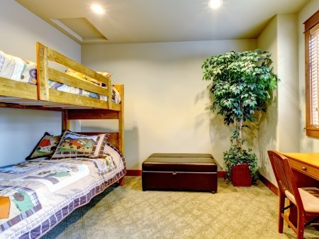 bedroom furniture: Bedroom with children double bed with desk and tree.