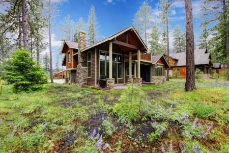 retreat: Mountain cabin home wood exterior with forest and flowers.