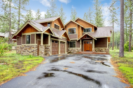 white trim: Mountain luxury home with stone and wood exterior, spring forest. Stock Photo