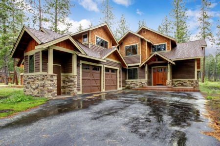 luxury house exterior: Large mountain cabin house with stone and driveway after rain. Stock Photo