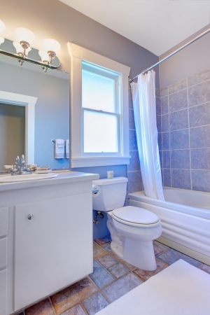 Blue bathroom with white cabinets with stone tiles and blue tiles. Stock Photo