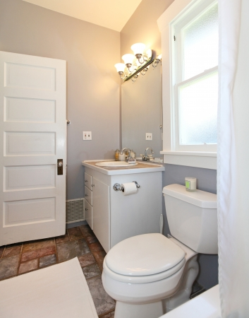 bathroom interior: GREY and white small bathroom with open door. Stock Photo