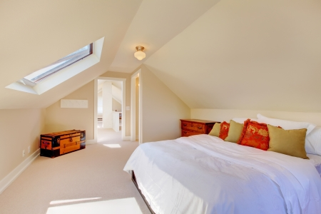Bright clean attic bedroom in the small home with beige carpet. photo