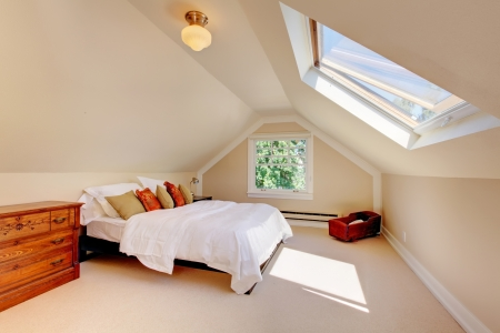 skylight: Attic modern bedroom with white bed and skylight and beige walls and carpet.