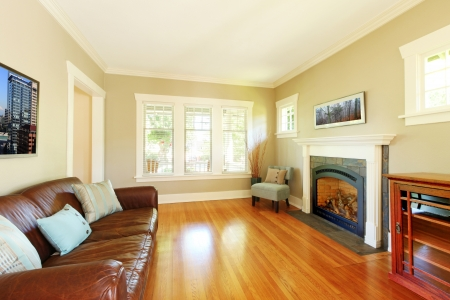Elegant living room with fireplace and leather sofa with cherry hardwood floor.