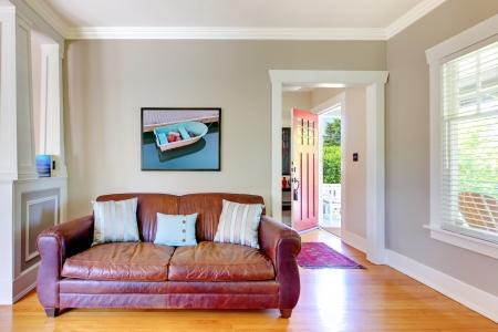 pokoj: Kožená sedačka a obývací pokoj s otevřenými dveřmi s šedými zdmi. Reklamní fotografie