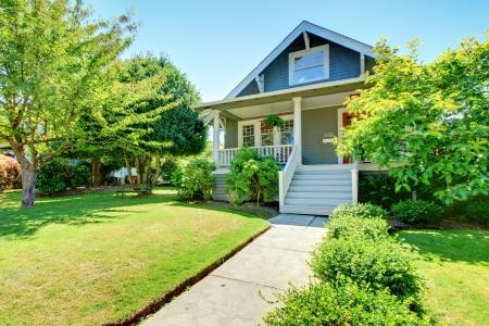 fachada de casa: Gris peque�a casa antigua americano exterior frontal con escalera blanca durante el verano.