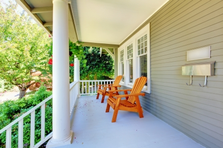 front porch: Porche frontal con sillas y columnas de una casa de estilo antiguo artesano. Foto de archivo