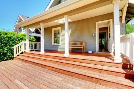 Back porch van kleine grijze huis met bank Dring zonnige zomerdag.