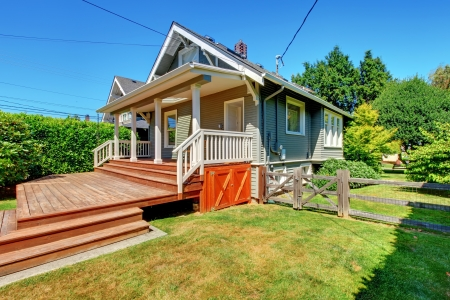 Small grey house with back large porch and old fence. Stock Photo - 16727884
