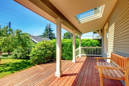 deck: Large covered porch with skylight and wood bench and floor with summer landscape.