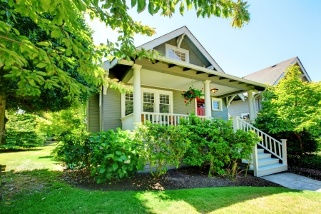 front of house: Grey small house with porch and white railings with summer landscape.