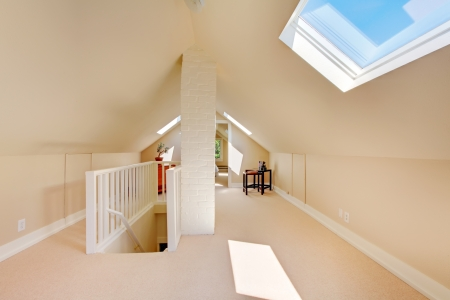 royalty free photo: Bright clean attic in the small home with beige carpet.