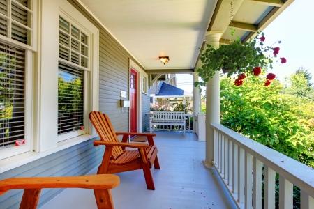 front porch: El porche delantero de la casa gris con barandillas blancas y dos ventanas con flores