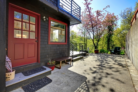 Front red door of black wood house with garden view during spring. Stock Photo - 16752302