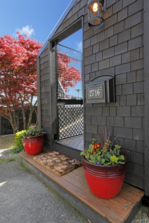 Black wood house with door and red flower pots with japaneas maple. Stock Photo - 16752355