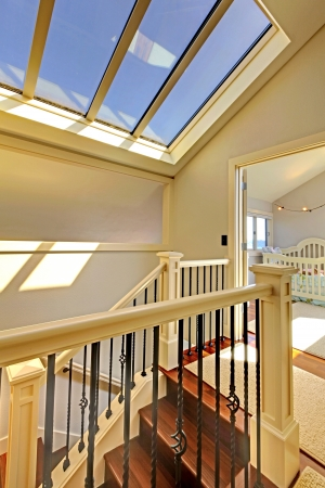 Staircase with skylight and baby room in a bright hallway.