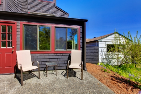 Two chairs next to red door and small black house with shed on the side. Stock Photo - 16752285