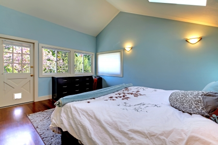 Blue bedroom with bed and skylight and cherry hardwood. Stock Photo - 16752364