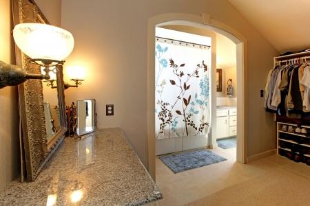 closet door: Large closet  room with door to bathroom with shower. Stock Photo