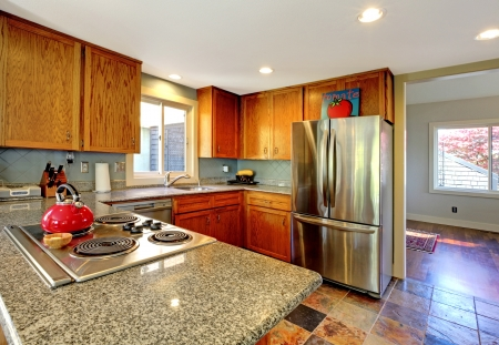furnished apartments: Kitchen with granite countertop stove and red tea pot.