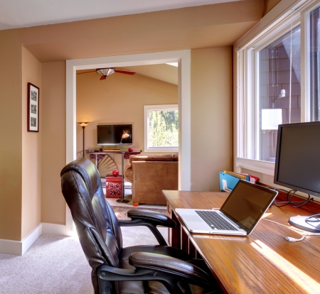 home office desk: Home office and computer and chair with brown walls and TV in living room. Stock Photo